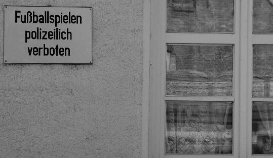 prohibtion sign 'You are forbidden by the police to play soccer'photographed from a different point of view