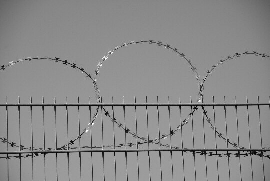 Razor barb wire at the top of a building site fence